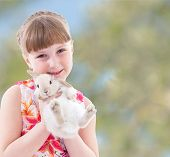 laughing girl holding a rabbit.