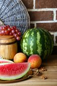 Composition of ripe watermelon, fruits and wooden barrel on  color wooden table, on bricks backgroun