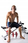 Muscular Blond Young Man Lifting Weights And Listening To Music In Headphones