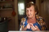 Elderly woman sitting at table in his house.