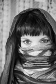 Young girl covers her face with a veil. Hijab. Black and white photo.