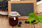 stock photo of jar jelly  - Blank slate blackboard in front of ripe blackberries and a jar blackberry jelly on a rustic wooden table - JPG