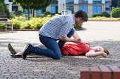Man Trying To Help Unconscious Woman