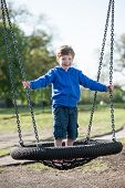 Boy standing on a large swing.