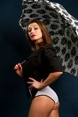 picture of nudist beach  - beautiful young brunette with a white umbrella on a dark background - JPG