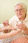 stock photo of old lady  - A young doctor giving medications  - JPG