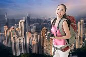 Happy smiling Asian young female backpacker with camera standing in front of skyscraper of Hong Kong, Asia.
