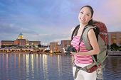 Happy smiling Asian young female backpacker with camera in Putrajaya, Malaysia.