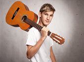 young man with acoustic guitar on a gray background