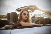 blonde girl sitting in a car wearing sunglasses