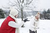 Happy couple doing a snowball fight together in winter