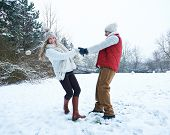 Happy couple dancing together in winter snow landscape