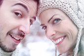 Smiling happy couple putting heads together in winter
