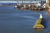 stock photo of workhorses  - A powerful push boat turning the barge in positions for docking - JPG