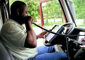African American Truck Driver Using A Onboard Computer And CB Radio