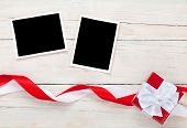 Photo frame cards and gift box with ribbon over wooden table background
