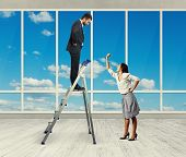 screaming woman and businessman on stepladder in the office with big windows
