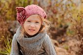close up autumn portrait of adorable child girl in pink knitted hat