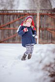 happy child girl in christmas hat with candy on the walk in winter snowy garden