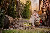 adorable happy child girl plays with egg box with herbs in early spring garden