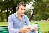 Young man listening music in a park