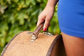 picture of mini-skirt  - Detail of antique hat case being held by girl wearing blue mini skirt - JPG