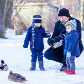 Father And Two Little Siblings Boys Feeding Ducks In Winter.