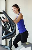 image of elliptical  - Happy woman doing exercises with elliptical trainer in gym - JPG