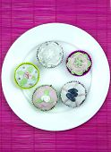 Five Decorated Muffins  On A Wooden And Pink Placemat