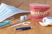 stock photo of dental  - Set of false teeth with dental cleaning tools including a toothbrush dental floss disposable face mask and plastic flossing tool in an oral hygiene concept - JPG