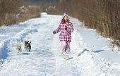 image of dog clothes  - Young girl in winter clothes running on snow with two dogs - JPG