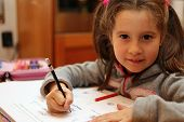 Beautiful Little Girl Writes The Homework On Notebook