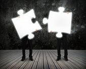 Glowing Puzzles Businessmen Hold To Connect Illuminating Dark Wooden Floor