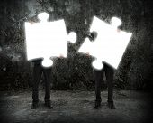 Glowing Puzzles Businessmen Hold To Connect Illuminating Dark Concrete Room