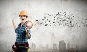 Young woman builder in hardhat screaming in megaphone