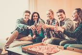Multi-ethnic friends with pizza and bottles of drinks having party