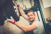 Mechanic checking wheel bearings in a car workshop