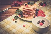 Healthy breakfast with pancakes, fresh berries and yoghurt on tablecloth in rural interior