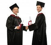 Cheerful young graduated student men shaking hands