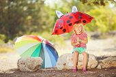 Little girl with a bright umbrella in the park.