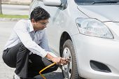Asian Indian driver checking air pressure and filling air in the tires of his car.