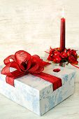 Celebration Gift Box With Red Candle On Wooden Background