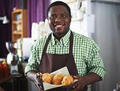 Happy African-american guy with croissants
