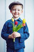 Cute little boy with bunch of red and yellow tulips