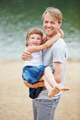 Happy father carrying young daughter in summer vacation on a beach