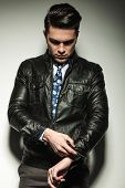 Business man in leather jacket, looking down while fixing his sleeve. On grey studio background.