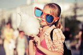 stock photo of candy cotton  - Happy teen girl eating cotton candy on the city street - JPG