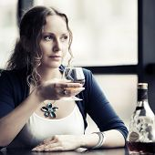 Beautiful young woman with cognac at restaurant