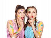 image of hush  - Two surprised Smeared in paint girl friends looking at the camera - JPG
