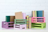 stock photo of crate  - Many books in crates on brick wall background - JPG